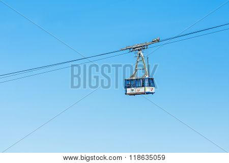 POIANA BRASOV ROMANIA - JANUARY 24 2016: Cable car transporting people in the resort Poiana Brasov with blue sky in the background
