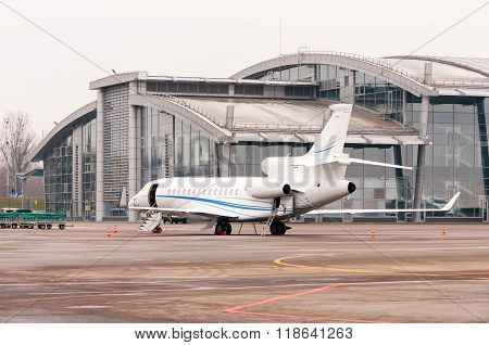 business jet airplane or aircraft with open door on airfield near of aeroport terminal
