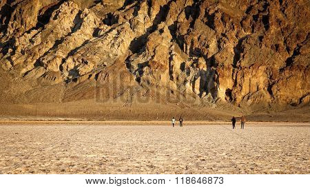 Tourists walk on the salt flats in Badwater Basin in Death Valley National Park. Badwater Basin in the lowest point in North America at 282 feet below sea level. poster