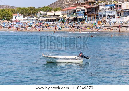 MATALA, GRETE - AUGUST 20, 2013: View on white motor boat and people at Matala beach, located on Crete island, Greece