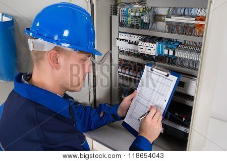 Young Male Technician Examining Fusebox