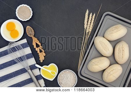 Bread dough rolls and baking ingredients with baking utensils, wheat sheaths and grain in a love spoon on grey slate background.