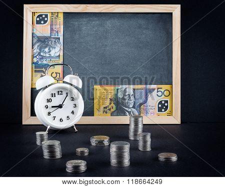 Vintage Clock, Blackboard, 50 Australian Dollars Bill, And Coin Towers On Black