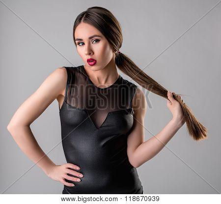 Sexy brunette in bodysuit posing as femme fatale