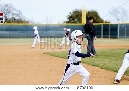 American little league boy wearing helmet running bases during a game while sticking tongue out. poster