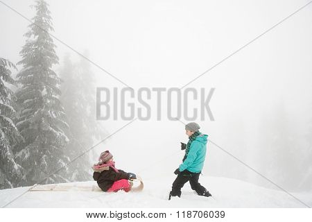 Mother and daughter with toboggan