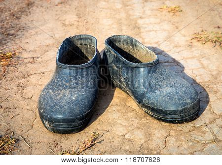 old lost galoshes on dry soil