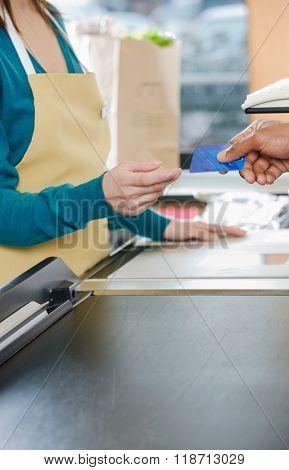 Customer handing a sales assistant a credit card