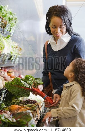 mother handing chard to her daughter