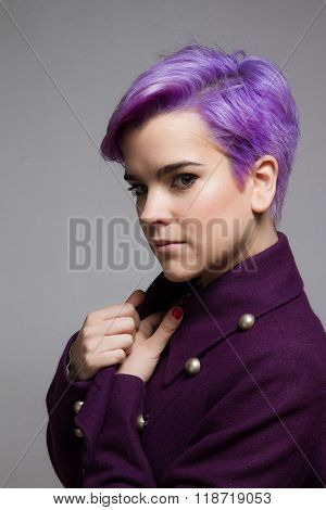 Violet-short-haired Woman Wearing A Violet Coat, Looking At Camera.