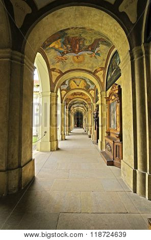 Enfilade of old Baroque building of catholic monastery Loreta in Prague. Enfilade is a suite of rooms formally aligned with each other. This was a common feature in grand European architecture from the Baroque period onward.