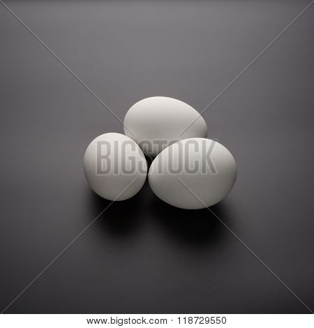 three white eggs on the black background