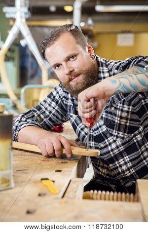 Smiling craftsman files wooden guitar neck in workshop