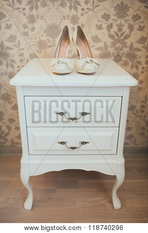 white bridal shoes on the wooden commode