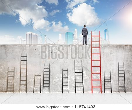 A businessman with hands in pockets standing on a concrete wall separating him from New York. Several ladders of different size at the wall blue sky above. Concept of reaching aim. poster