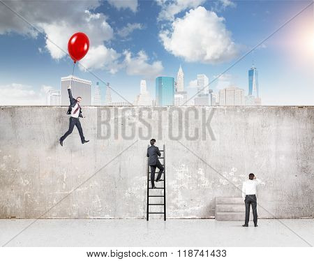 A businessman flying a red balloon a businessman climbing a ladder and one standing at a concrete wall separating them from New York blue sky above. Concept of reaching aim. poster