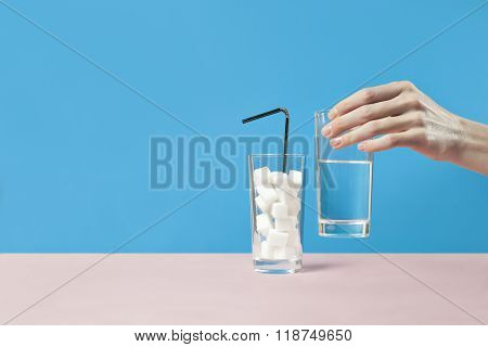 Glass of water against sugar, diabetes disease, sweet addiction, hand take a glass