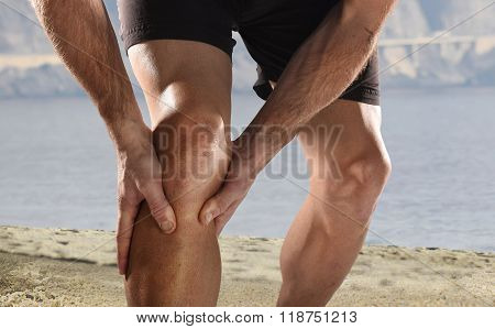 Young Sport Man With Athletic Legs Holding Knee In Pain Suffering Muscle Injury Running