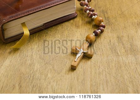 Catholic wooden cross with a crucifix on the book poster