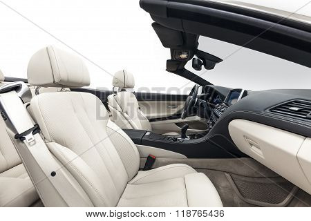 Car cabriolet interior with white seats, dashboard & steering wheel