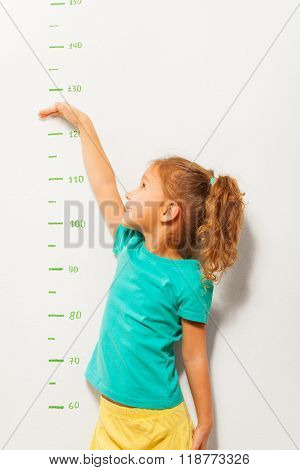 Little girl shows her height on a scale on the wall once she grow up