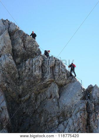 Mountaineers climbing the via ferrata climbing route at mountain Watzmann with blue sky