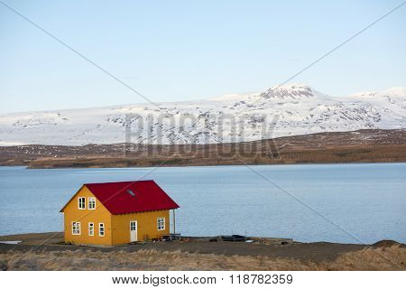 Quaint cottage home house in iceland, overlooking water fjord and snowy mountains in distance