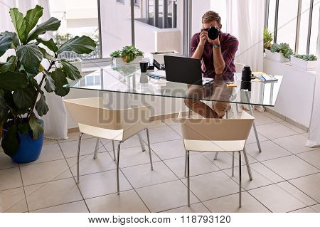 Professional photographer sitting in his home studio