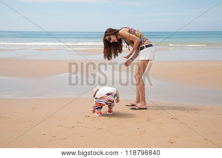 Baby And Mother Looking For Sea Shells