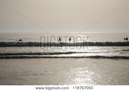 Backlighting Surfers Waiting Waves