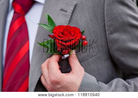 groom in red tie with rose on his jacket