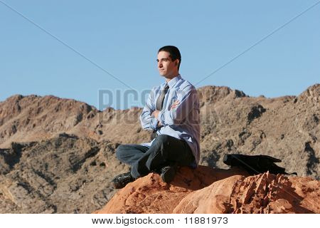 Stressed businessman meditating outdoors