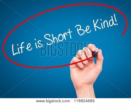 Man Hand Writing Life Is Short Be Kind! With Black Marker On Visual Screen