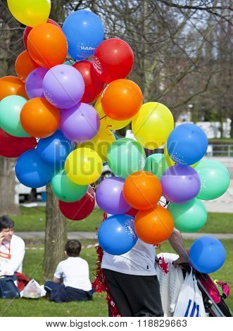 CLACTON ON SEA, ESSEX, ENGLAND, UK- 1 JULY 2015- a man pushing his small baby in a pushchair in the park, and holding multicolored balloons.
