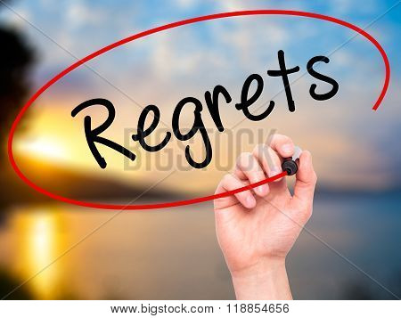 Man Hand Writing  Regrets With Black Marker On Visual Screen