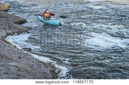 male kayaker is paddling upstream of turbulent river with a fast flow