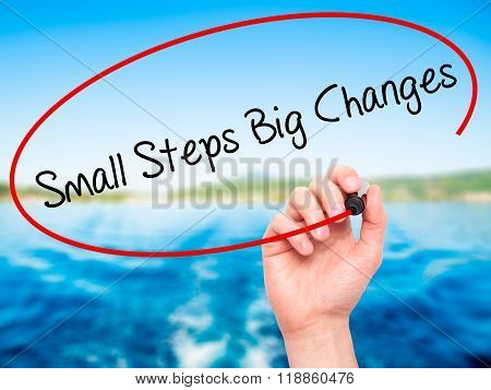 Man Hand Writing Small Steps Big Changes With Black Marker On Visual Screen