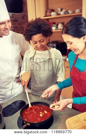 cooking class, culinary, food and people concept - happy group of women and male chef cook cooking tomato souse in kitchen