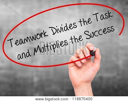 Man Hand Writing Teamwork Divides The Task And Multiplies The Success With Black Marker On Visual Sc
