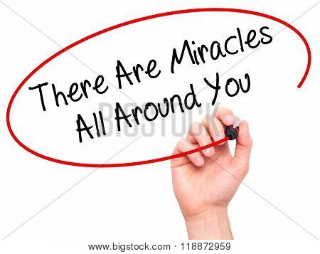 Man Hand Writing There Are Miracles All Around You  With Black Marker On Visual Screen