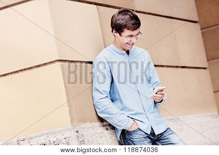 Young hispanic man wearing glasses, blue shirt and jeans, leaning on building wall, holding smartphone in his hand, reading message and attractive smiling - communication or humor concept