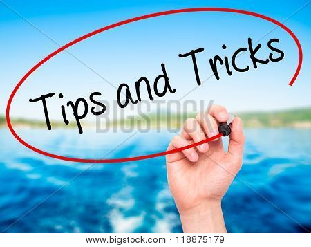 Man Hand Writing Tips And Tricks With Black Marker On Visual Screen