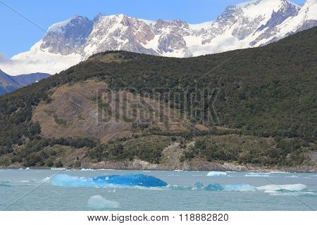 Snow capped mountain and blue iceberg in a glacial lake