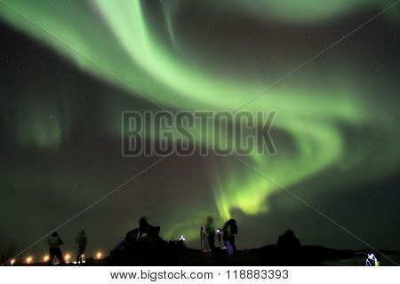 People braving the cold to watch and photograph the Northern lights. Tromso, Norway.