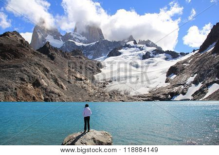 Girl, blue lake, glacier and mountains