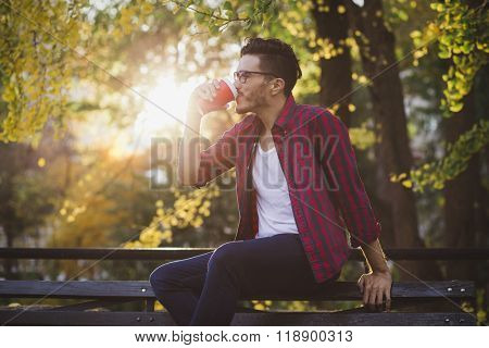 Young man with a cup of coffee. New York city, Central Park in an autumn day.
