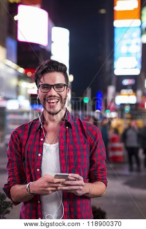 Man with earplugs and smartphone on Times Square, New York, at night.