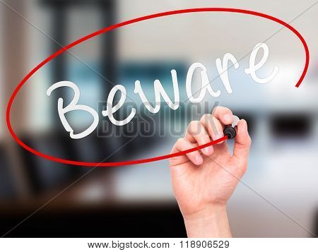 Man Hand Writing Beware  With Marker On Transparent Wipe Board