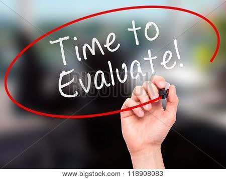 Man Hand Writing Time To Evaluate With Marker On Transparent Wipe Board