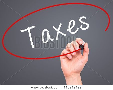 Man Hand Writing Taxes With Marker On Transparent Wipe Board